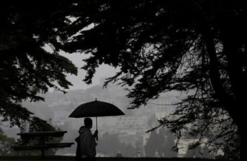A man and woman walk along a path under trees at Alamo Square Park in San Francisco, Thursday, March 3, 2016. Light rain has started in the San Francisco Bay Area as the region braces for a series of storms expected this weekend and into next week. (AP Photo/Jeff Chiu)